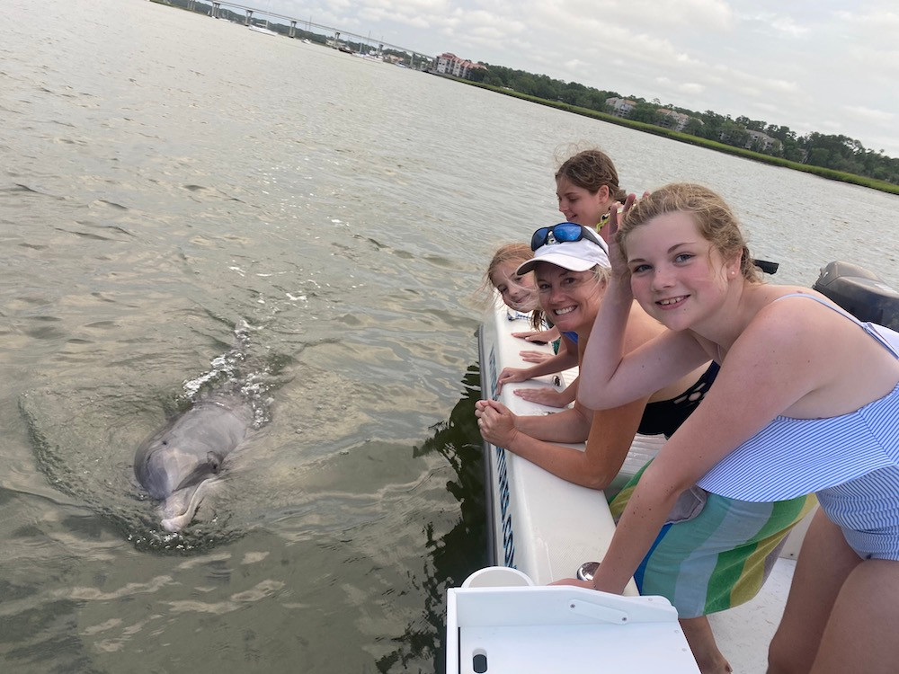 mom and daughters leaning over boat looking at dolphin