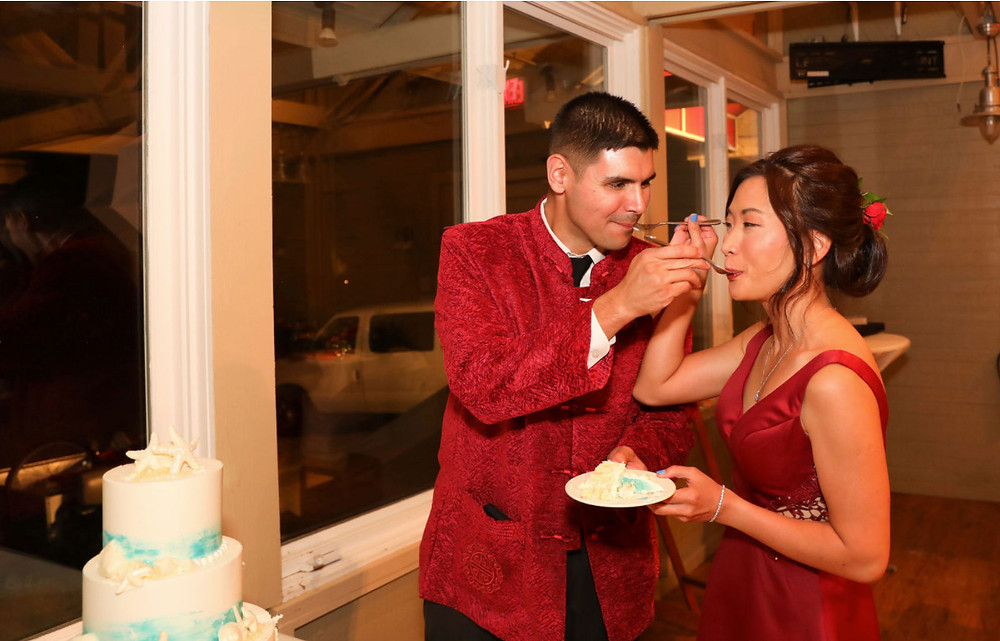 bride and groom in red outfits eating cake