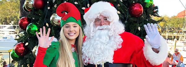 elf and santa waving in front of tree at marina