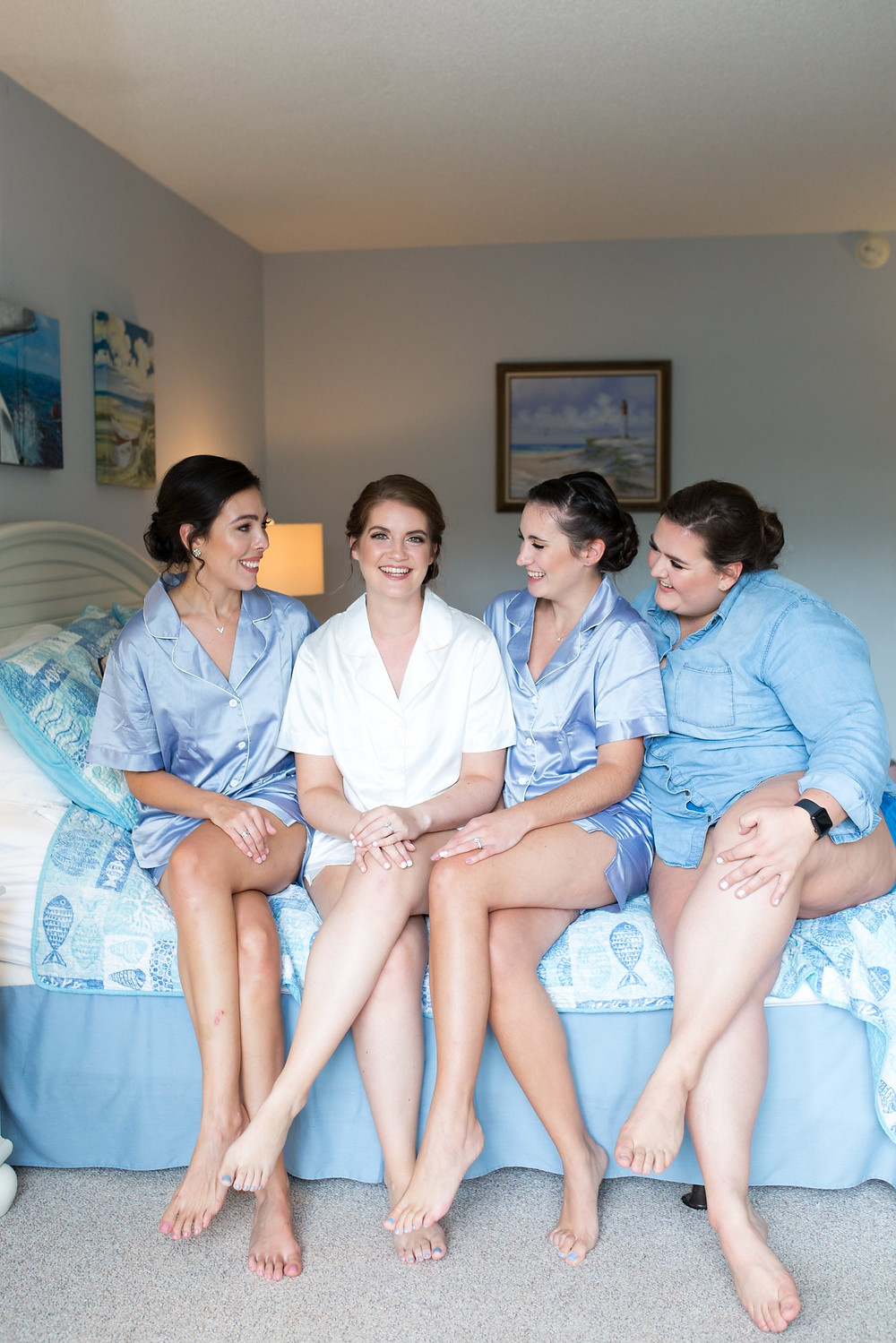 bride with bridesmaids in blue sitting on bed