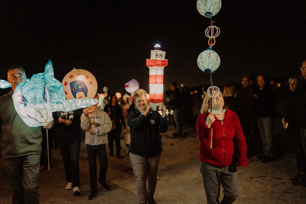 participants hold their lanterns proud as they walk the beach