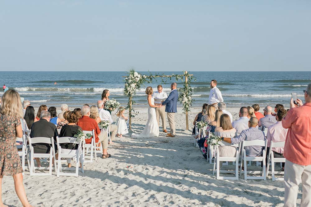 guests watching wedding ceremony on the beach