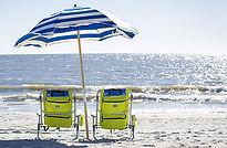 yellow beach chairs and umbrella