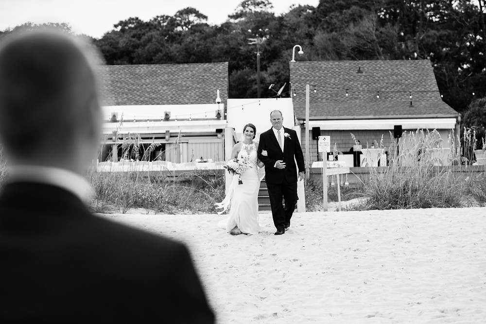 father of the bride walking bride down to groom on beach