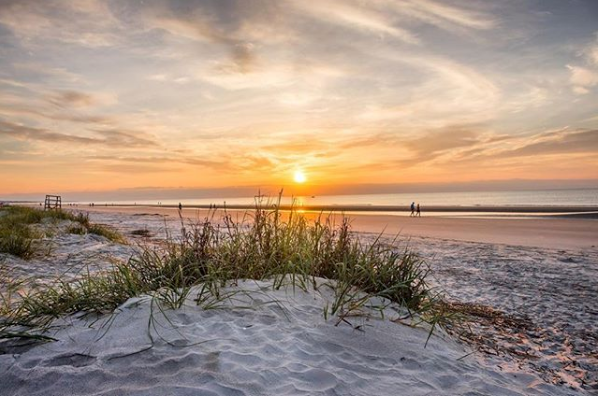 sunrise over dunes of palmetto dunes with couple walking on beach