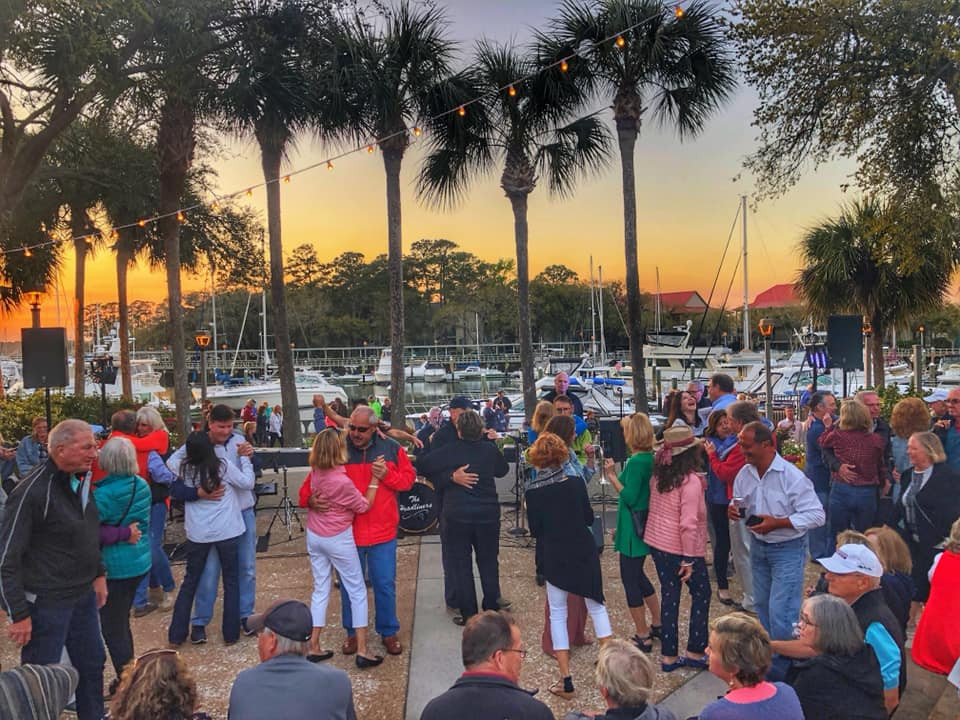 couples dancing with Shelter Cove marina and sunset in background