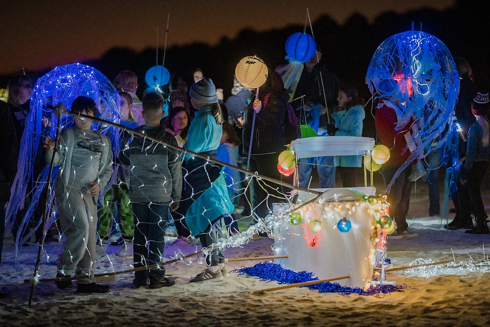 a lit up boat lantern rests on the beach with blue laterns in the background