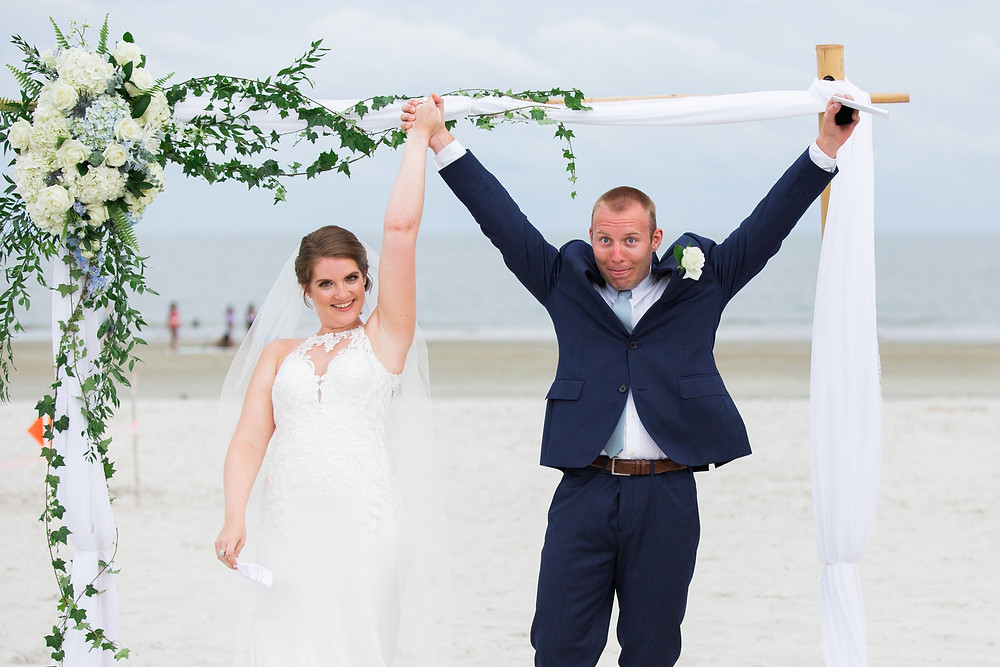 bride and groom celebrating after beach ceremony