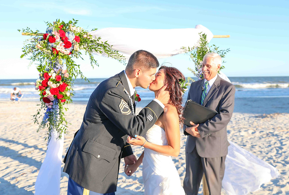 bride and groom kissing on beach ceremony