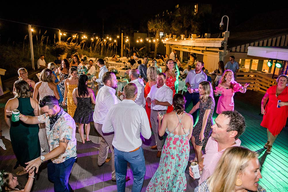 guests dancing at night under the lights during wedding reception