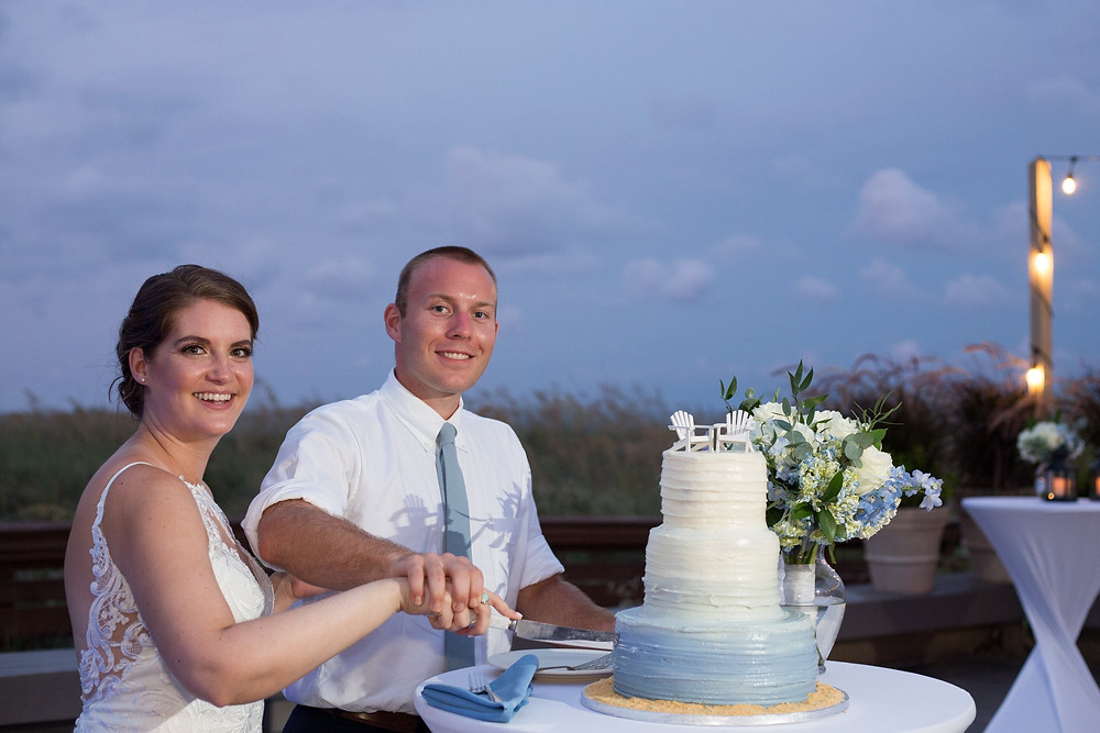 bride and groom cutting wedding cake in the evening