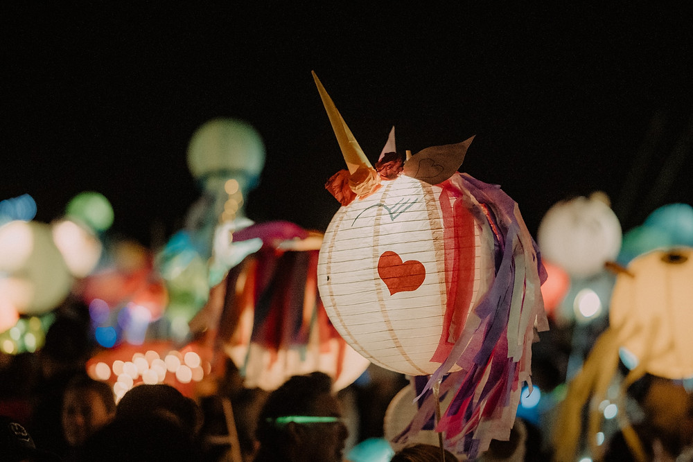 a unicorn lantern with a heart lights up the sky with other lanterns