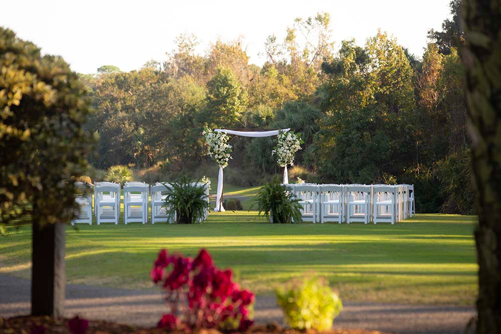 ceremony chair and arch setup with tree backdrop