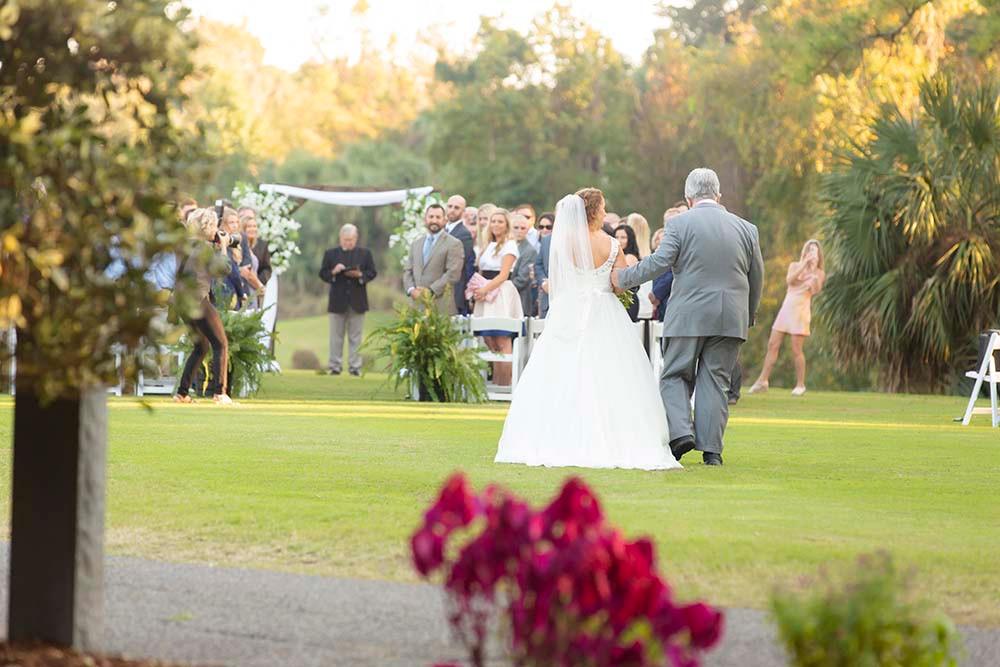 bride and father walking towards ceremony site