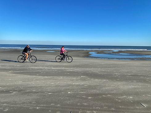 man and woman biking on beach