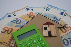 A green calculator, with a wooden house,