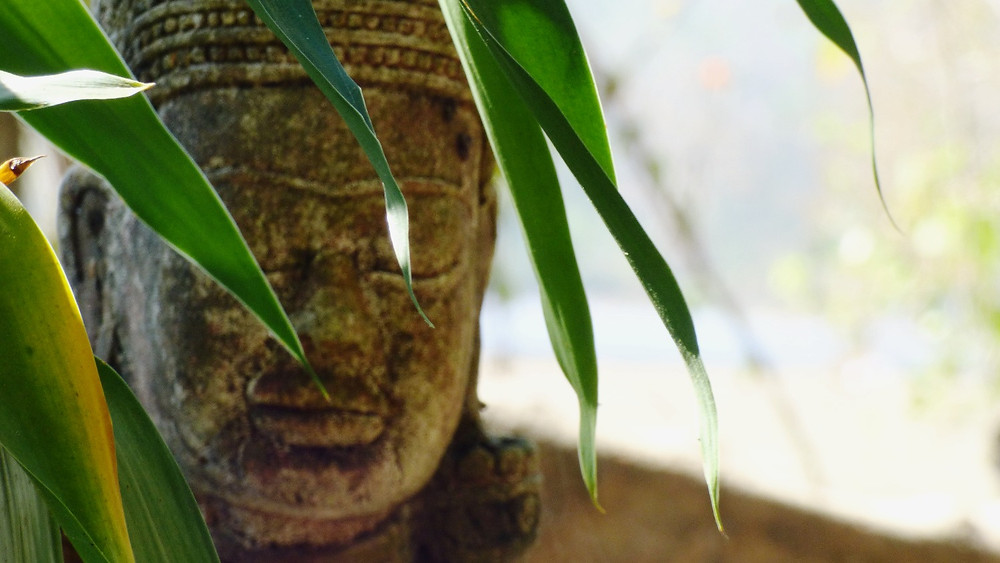 Buddha statue with leaves in foreground, Pai, Thailand