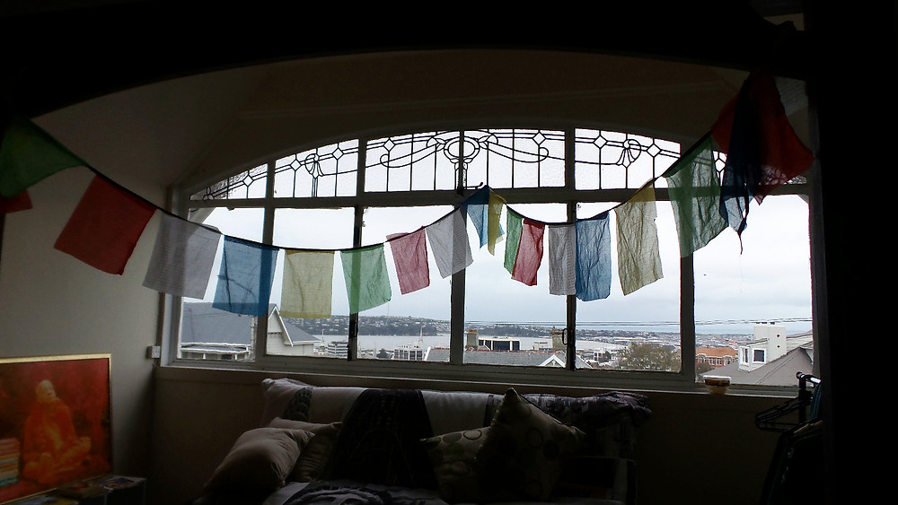 Putting up our Tibetan prayer flags in our room in Dunedin