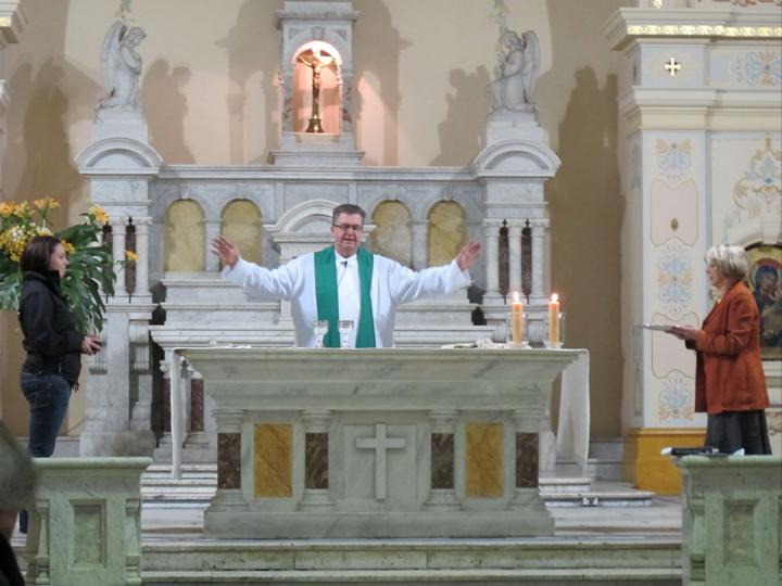Fr John receiving gifts at altar, Sacred Heart
