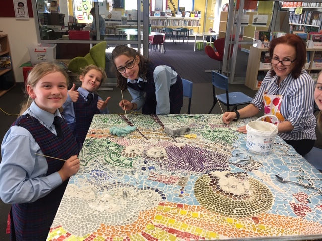 Children and art teacher Bec making the mosaic