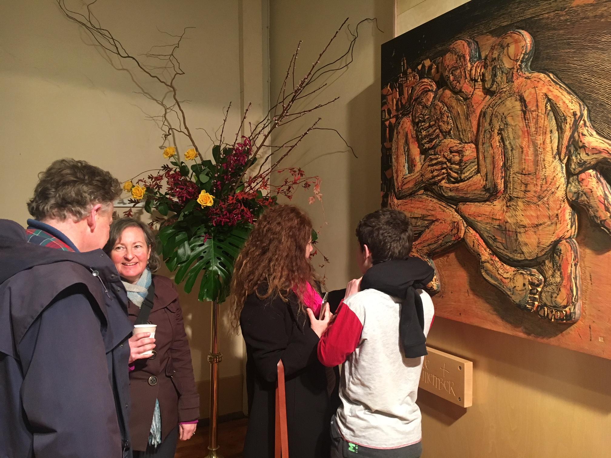 People admire memorial carving at Sacred Heart church