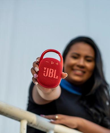 Moça segurando caixa de som JBL Flip