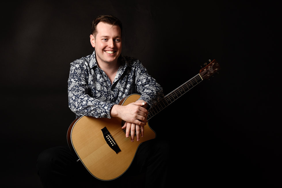 Shane Hennessy holding his guitar