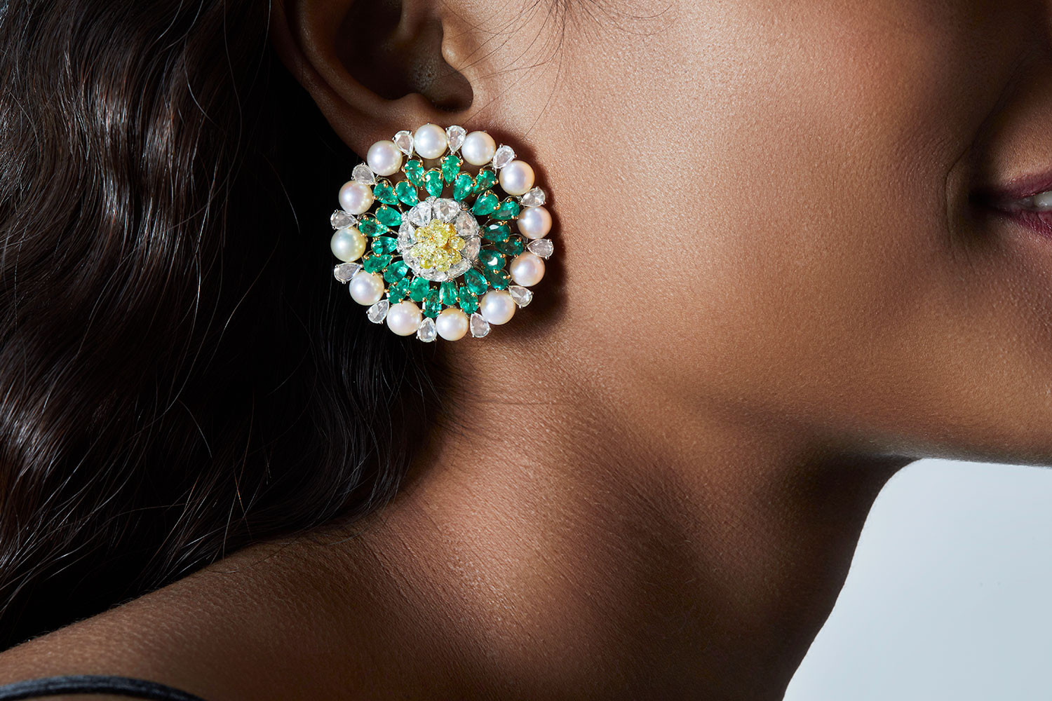Earrings composed with rose-cut diamonds (pear-shaped), emeralds (pear-shaped) and elegant pearls as accents. The gemstones are alternatingly placed at various levels, creating a three-dimensional form that reflects brilliance and our signature artistry.  Featuring a bud-like lotus motif.