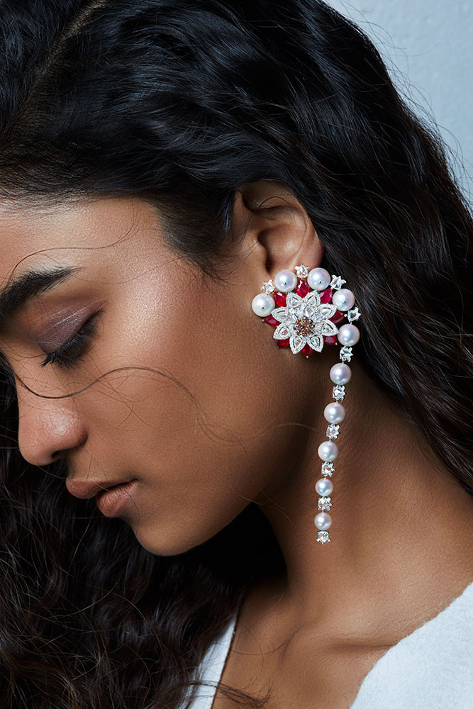Rich, lotus-inspired earrings composed of pear-shaped rubies and rose-cut diamonds, brilliant round diamonds and diamond briolettes. The gemstones create a dramatic three-dimensional form while minute micro-paving of diamonds on petals at the base conveys precision.   Featuring a blossomed lotus motif.
