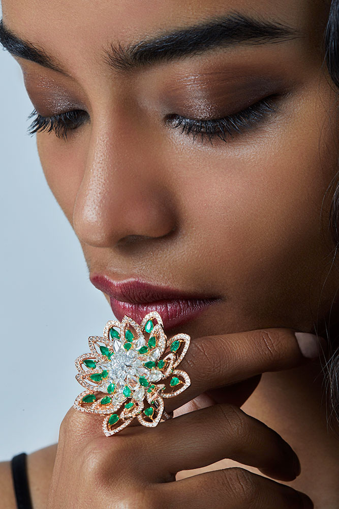 Emeralds with mixed-shape diamonds, handcrafted with flawless precision on two tones of gold. The form celebrates the lotus and accentuates it as a bold, statement piece.  Featuring a blossomed lotus motif.