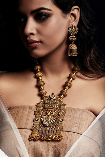 Hand-crafted gold necklace and earring suite evoking the glory of tradition.
