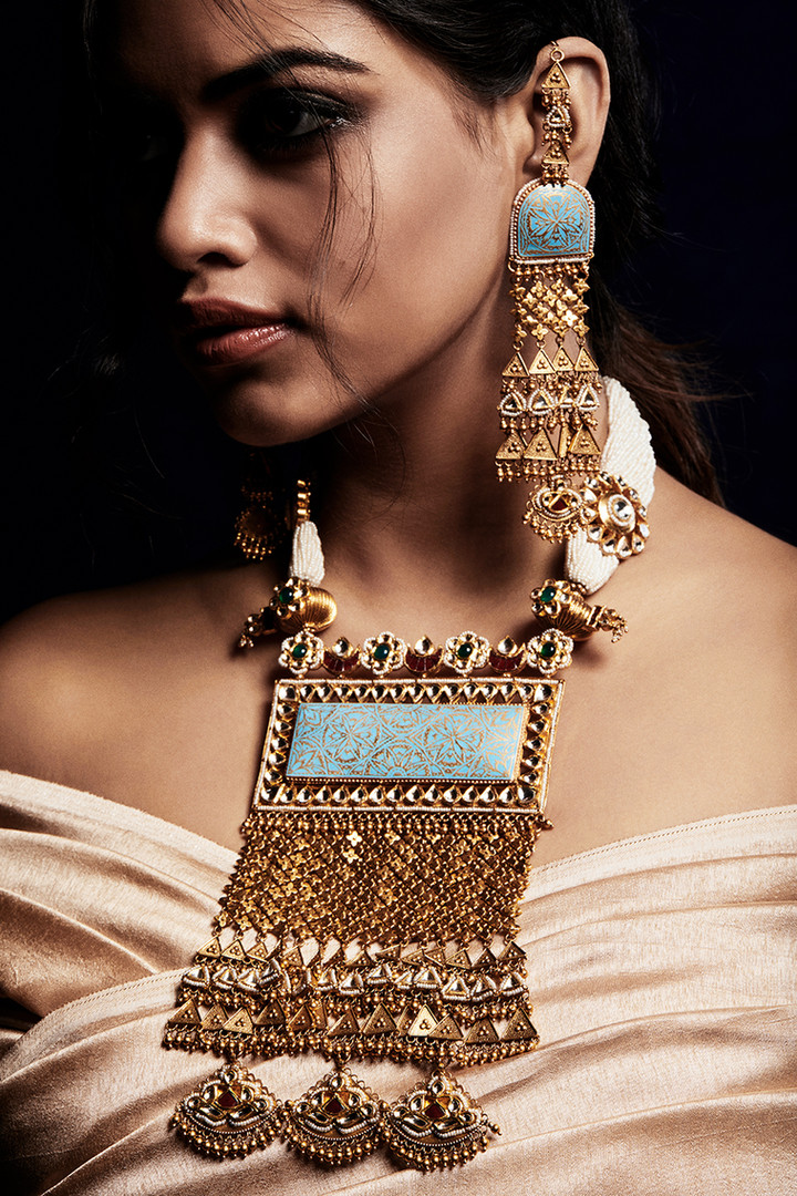 An arresting gold necklace and earring suite with diamond polkis, emeralds and ruby accents.