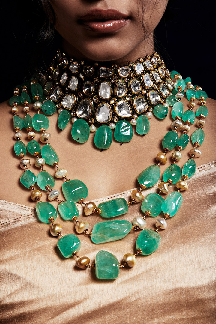Multi-layered emerald strings with pearl accents, exemplifying high style.