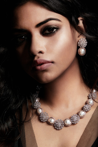 Pear-shaped diamonds, featured as flower petals together with south-sea pearls, made over two-tones of gold.