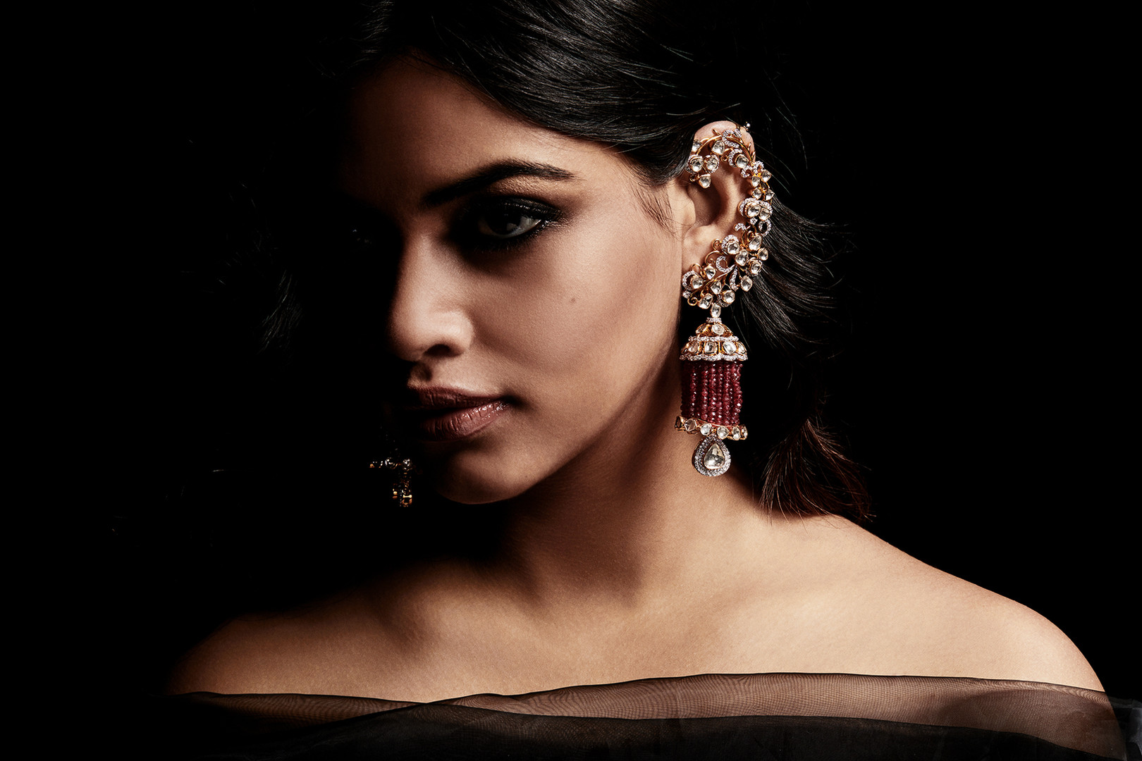 A signature-modern creation of diamond polki jhumkis with ear cuffs and ruby tassles.