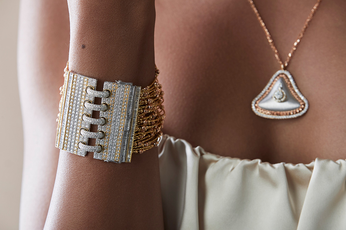 Statement cuff featuring stacks of gold chains, strung on with gold beads and diamonds.