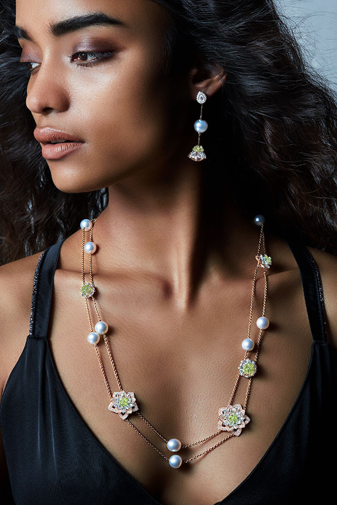 A chic, modern neck piece featuring rose-cut and full-cut white diamonds and yellow diamond briolettes with elegant pearl accents, accented by gem-laden lotuses that bloom amidst these strings.  Featuring both; a bud-like and blossomed lotus motif.