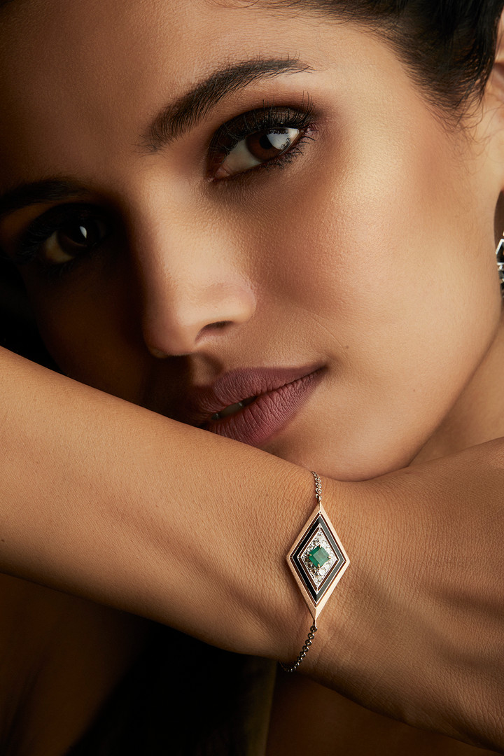A CHIC DECO CHARM FEATURING DIAMONDS & EMERALDS, WITH BLACK ENAMEL & BRUSHED GOLD FINISH.