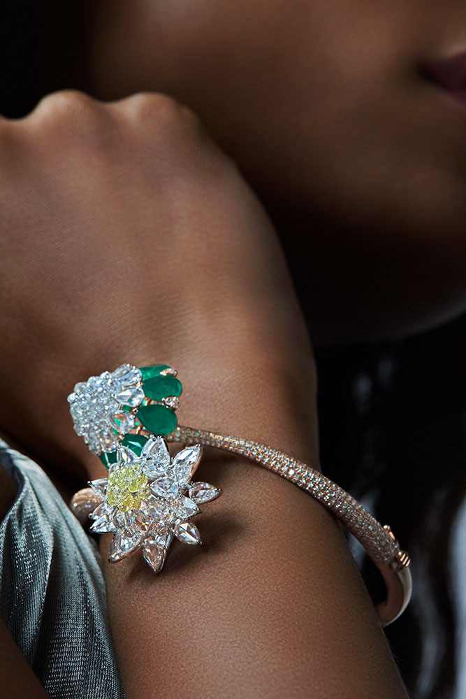 A unique, asymmetric bracelet, with an easy to open mechanism, composed of two tones of gold. It features rose-cut diamonds, yellow and white diamond briolettes as the top bunch while brilliant-cut diamonds are set in micro-pave on the arms of the bracelet.   Featuring both; a bud-like and blossomed lotus motif.