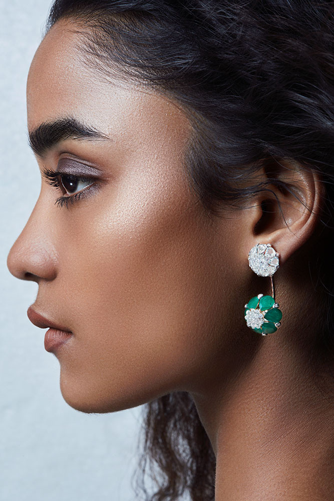Delicate earrings featuring pear-shaped emeralds and rose-cut diamonds, full-cut round diamonds and diamond briolettes. The emerald tones demurely draw out the formation and create a tender lotus bud.  Featuring a bud-like lotus motif.