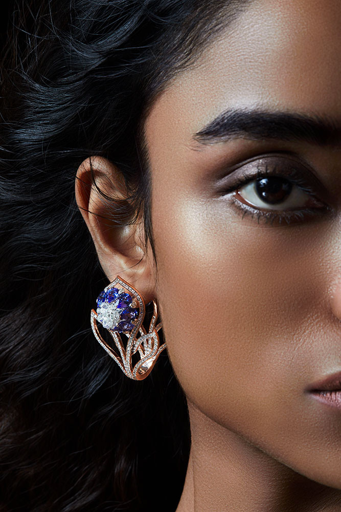 Contemporary earrings featuring pear-shaped blue sapphires, brilliant round diamonds and diamond briolettes. The shape extends the lotus as a tendril to add a unique dimension to the design.   Featuring a bud-like lotus motif.