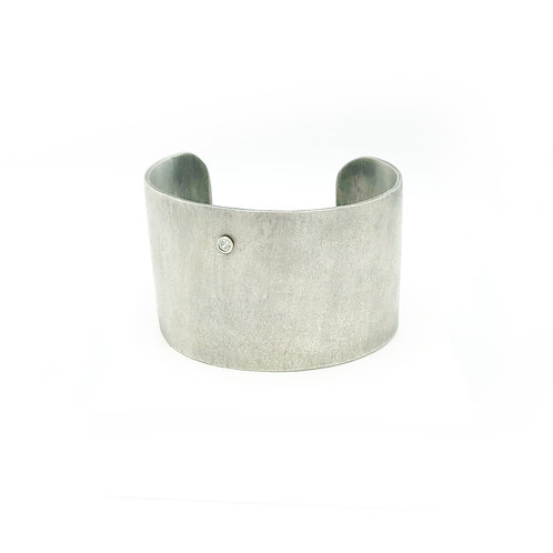 Textured and oxidized sterling silver bold cuff bracelet featuring white topaz.