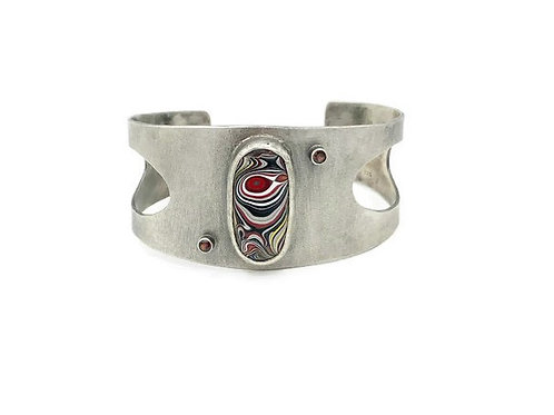 A sterling silver open Fordite cuff bracelet featuring a 3mm red garnet and set in sterling silver.