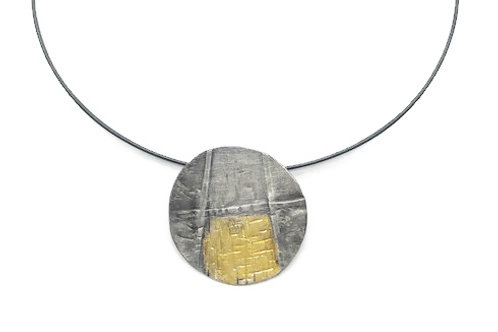 A fold forming small pendant necklace mixed with sterling silver and 24K gold.