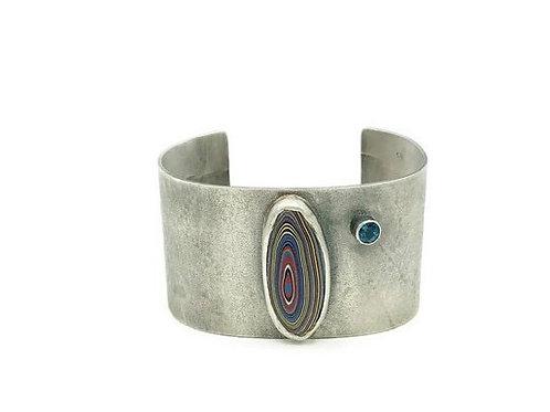 A Fordite gemstone cuff with London Blue Topaz.