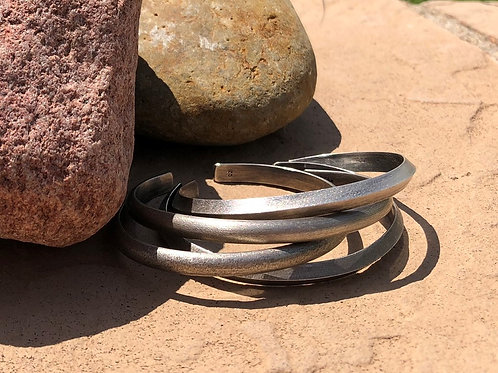 A stack of single triangle cuff bracelets in sterling silver against a rock.
