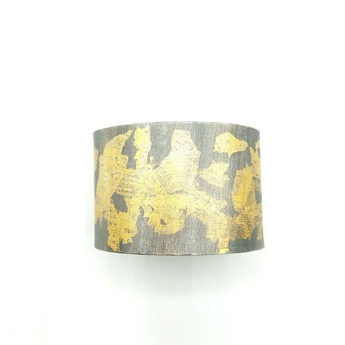 Abstract bold cuff bracelet in textured and oxidized sterling silver and 23K gold foil.