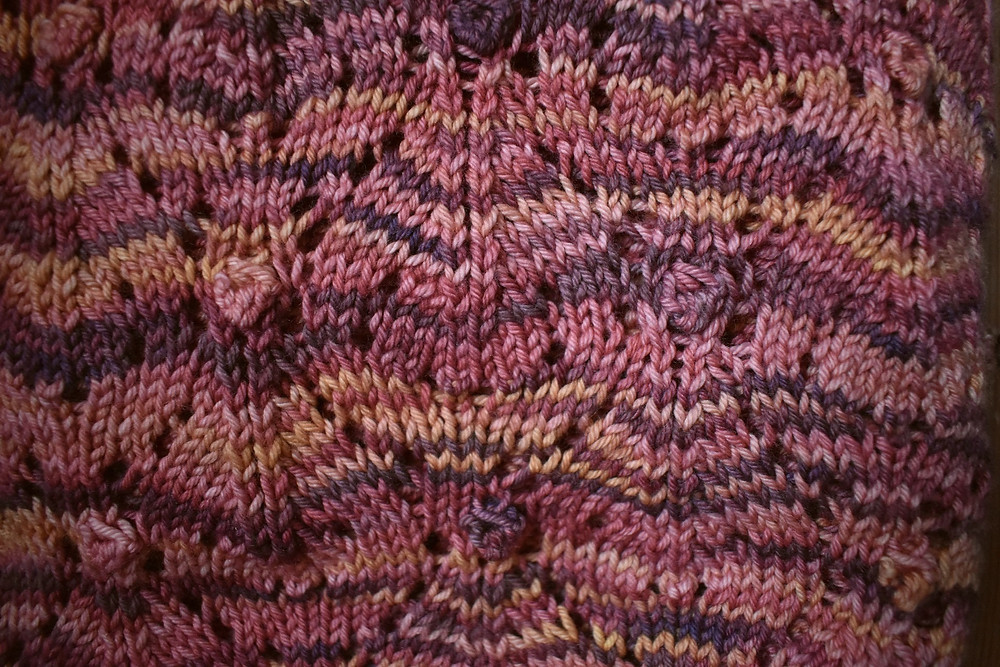 Close up of the Together lace and bobble pattern knit in Meet Me on the Hill colorway, pinks, golds and purples
