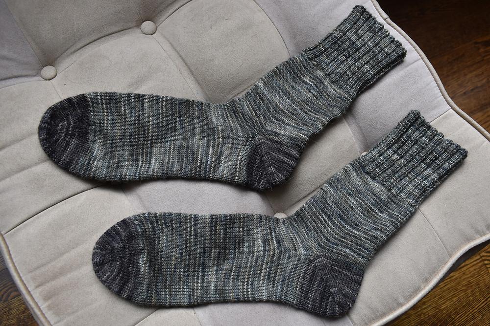 Dark brown and grey socks on a beige ottoman