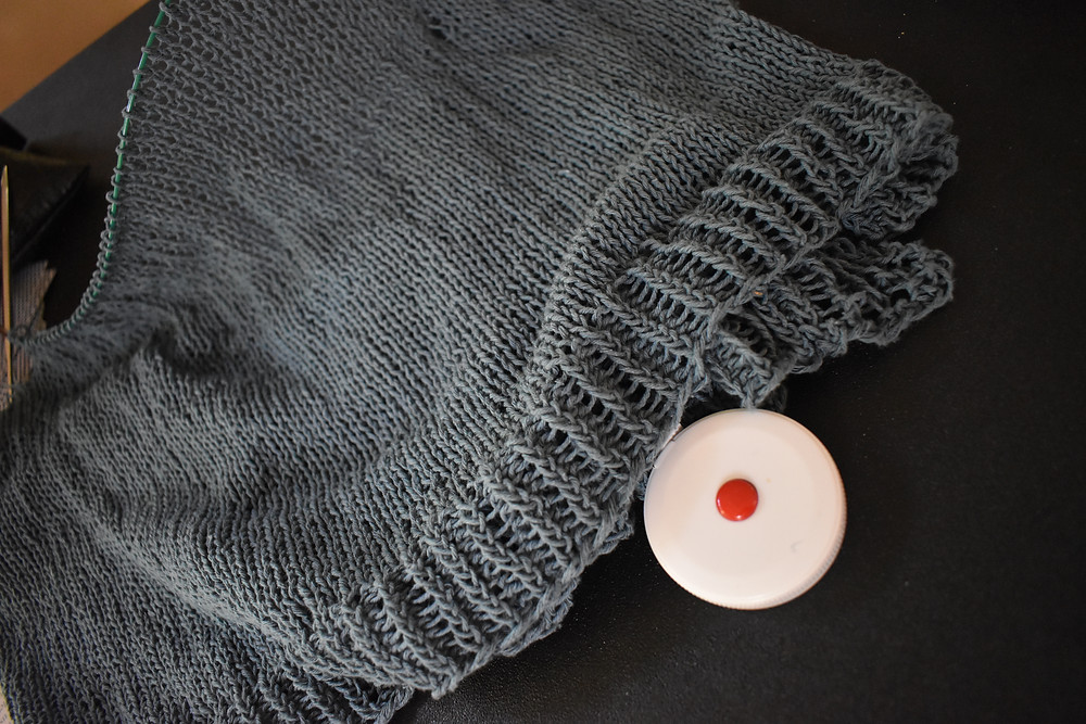 Partially knit sweater with white tape measure